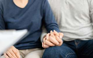A grieving elderly couple holding hands