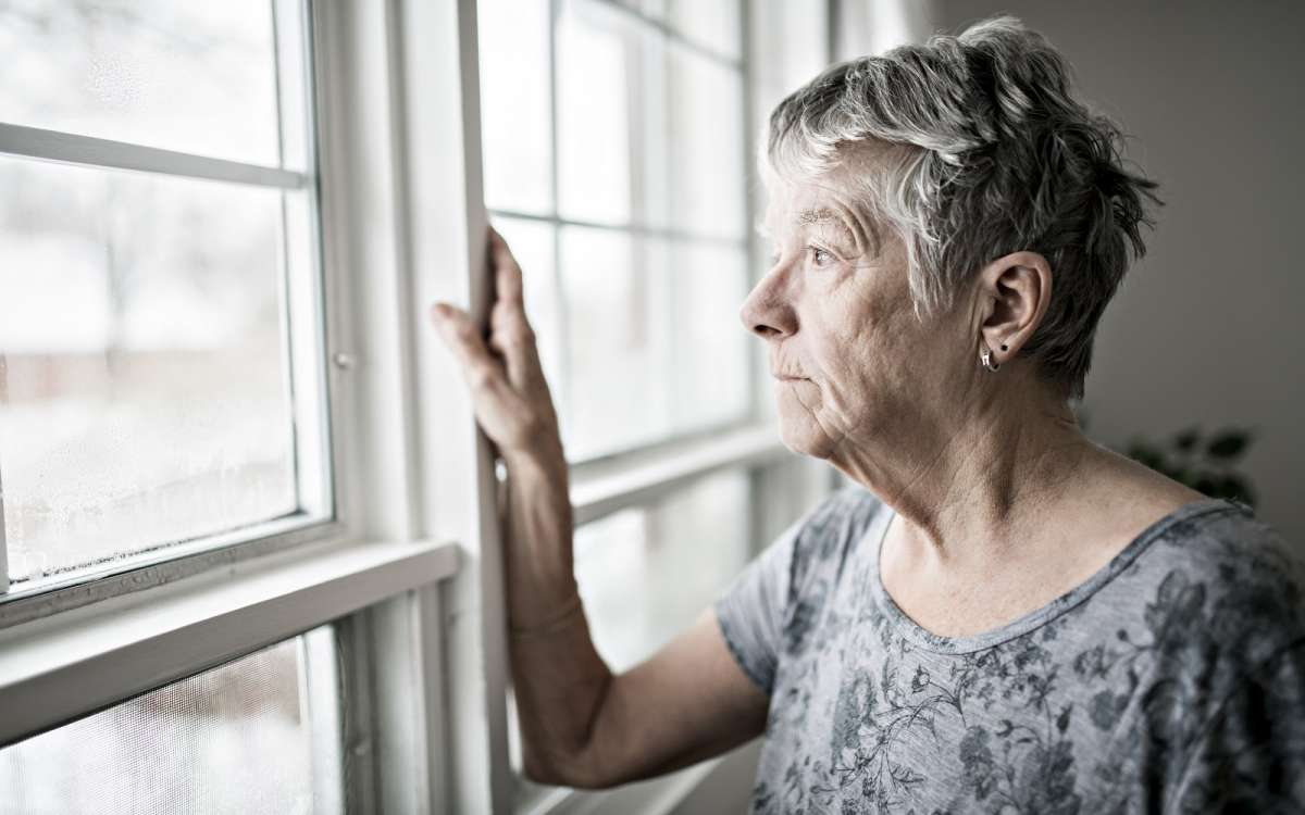an upset elderly woman looking out the window