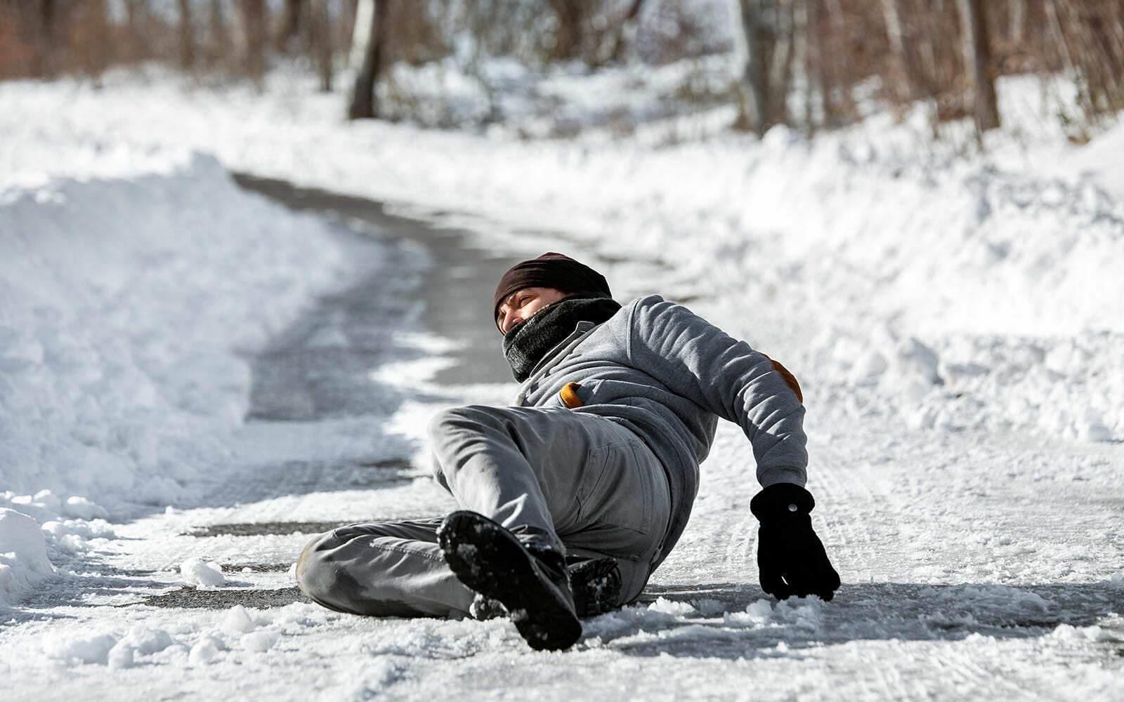 Male worker lying on the ground after slipping on ice
